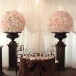 Mesa marrom com pedestais de flores rosas