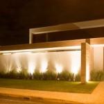 O muro iluminado com focos de luz compõe a fachada