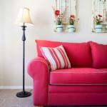 Almofada com listras decora com sofá vermelho, combinando uma das cores.