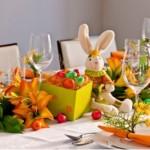 O coelho de pelúcia decora a mesa junto com flores e ovos coloridos.