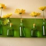Garrafas de vidro se transformaram em vasos de flores.