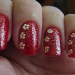 Unhas com base vermelha e glitter, decorada com flores pequenas