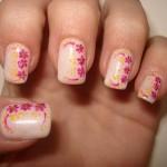 Unhas com base nude e flores rosas com detalhes em amarelo