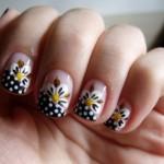 Unhas com francesinha preta e bolinhas brancas, decorada com flores