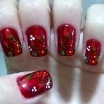 Unhas com fundo vermelho e decoração com flores e pimentas vermelhas