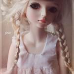 Boneca loira de tranças com feições delicadas