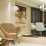 Lareira instalada numa base de alvenaria coberta com mármore na cor creme, ela fica posicionada entre dois ambientes.
