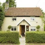 Fachada rústica estilo inglês, pé direito alto com janelas pequenas.
