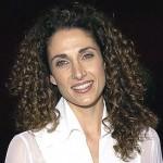 Melina Kanakaredes com cabelos longos extremamente encaracolados.