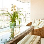 Poltronas confortáveis com almofadas claras e mesa de vidro ampliam o ambiente, além de proporcionar certo requinte.