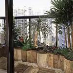 As cantoneiras de madeira dão o acabemto perfeito como divisória no jardim dentro da varanda.