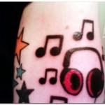 Tatuagem de notas musicais, estrelas e fone de ouvido no braço. (Foto: divulgação)
