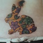 Tatuagem de coelho decorado com flores coloridas na barriga. (Foto: divulgação)