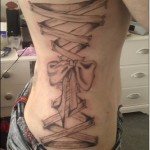 Tatuagem feminina laço de fita nas costelas. (Foto: divulgação)