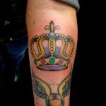 Tatuagem de coroa com pedras coloridas no braço. (Foto: divulgação)
