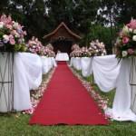 Tapete vermelho e arranjos cor de rosa.