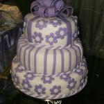 Bolo em camadas decorado com listras e flores lilás (Foto: divulgação)