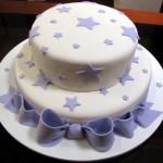 Bolo redondo com duas camadas decoradas com estrelas lilás de vários tamanhos e laço lilás feito de pasta americana (Foto: divulgação)