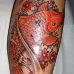 Tatuagem de carpa vermelha com flores na perna (Foto: divulgação)