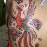 Tatuagem de fênix feminina decorada com flores (Foto: divulgação)