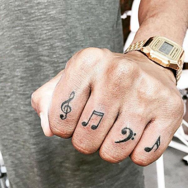 Tatuagem notas musicais nos quatro dedos da mão masculino (Foto: Reprodução)