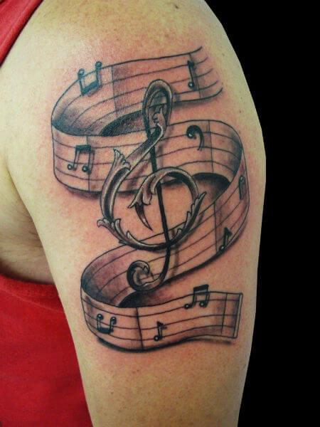 Tatuagem Clave de sol envolvida por notas musicais no braço (Foto: Reprodução)