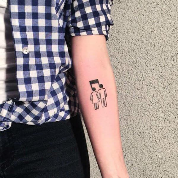Tatuagem de nota musical com casal (Foto: Reprodução)
