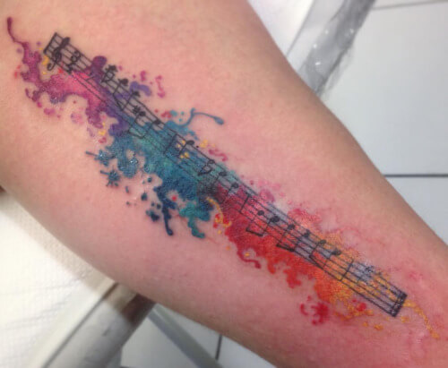 Tatuagem de notas musicais coloridas no braço (Foto: Reprodução)