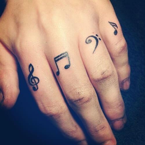 Tatuagem notas musicais nos quatro dedos da mão feminino (Foto: Reprodução)