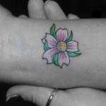 Tatuagem pequena de flor no pulaso (Foto: divulgação)