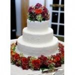Bolo branco de andares decorado com flores coloridas (Foto: divulgação)