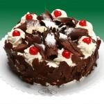 Bolo redondo decorado com lascas de chocolate e cerejas (Foto: divulgação)