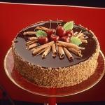 Bolo decorado com calda de chocolate e cerejas (Foto: divulgação)