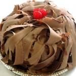 Bolo decorado com lascas grandes de chocolate e cerejas (Foto: divulgação)