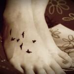 Tatuagem de andorinhas pretas no pé (Foto: divulgação)