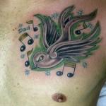 Tatuagem masculina de andorinha verde com notas musicais (Foto: divulgação)