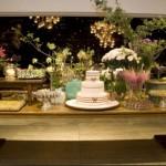 Mesa de madeira foi decorada com o bolo e muitos arranjos. (Foto:Divulgação)