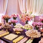 Muitos doces e flores na decoração da mesa de madeira. (Foto:Divulgação)
