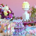 Os doces coloridos decoram a mesa principal junto com os arranjos de flores. (Foto:Divulgação)