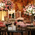 Mesa do bolo enfeitada com arranjos de flores. (Foto:Divulgação)
