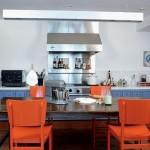 Cadeiras na cor laranja chamam atenção na cozinha. (Foto:Divulgação)