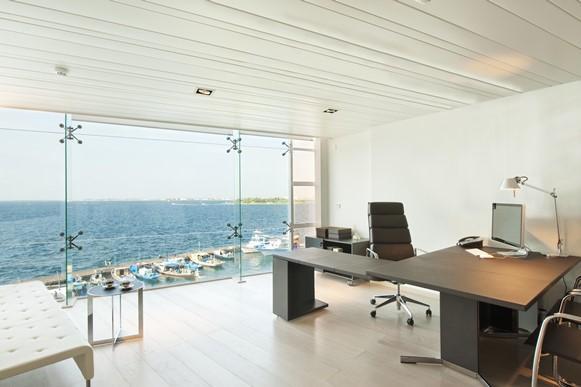 Home office com paredes de vidro. (Foto: Reprodução/Homegoid)