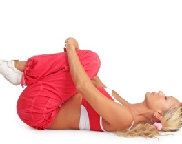Blonde sportive girl laying on her back and relaxing after the training