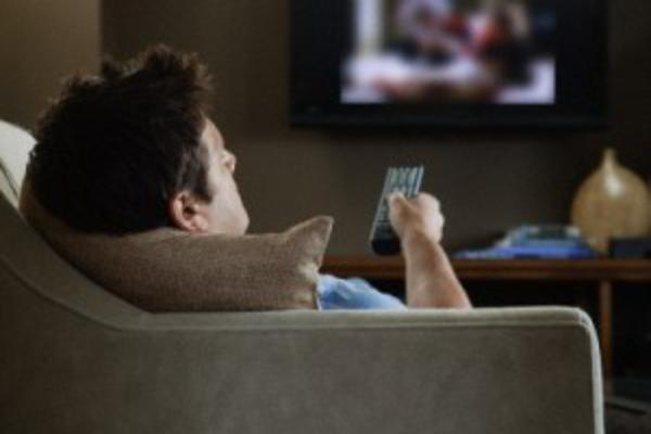 Homem sentado em frente à TV